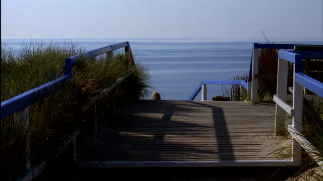 a woman walks up wooden steps at a beach - sylt stock videos & royalty-free footage