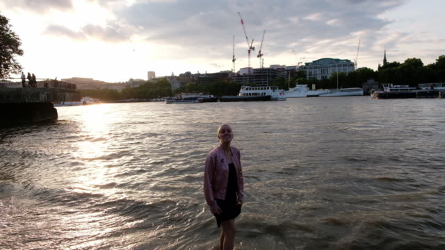 Woman walks with her feet in the Thames River in London, England during sunset.