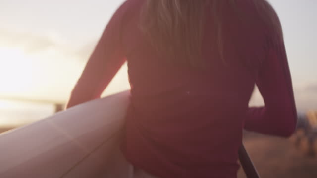 vídeos de stock e filmes b-roll de woman walks with paddleboard at dawn, slow motion - vista traseira