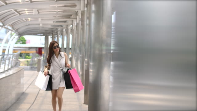 woman walks with shopping bags - shopaholic stock videos & royalty-free footage