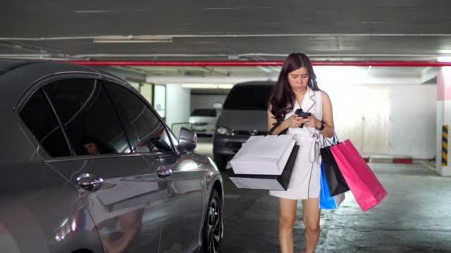 vidéos et rushes de femme marche avec des sacs à provisions - shopaholic