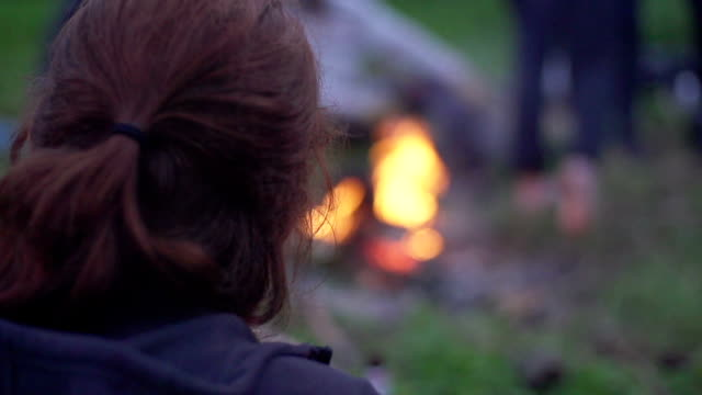 donna che si scalda vicino al fuoco. campeggio - solo ragazze video stock e b–roll