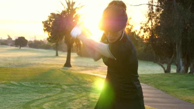 ms woman warming up on tee before early morning round of golf - east asian ethnicity stock videos & royalty-free footage