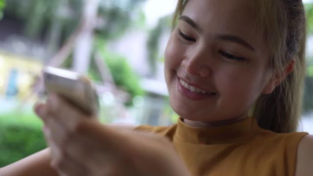 vídeos y material grabado en eventos de stock de mujer estaba jugando un teléfono móvil en la tienda de café. - sólo mujeres jóvenes
