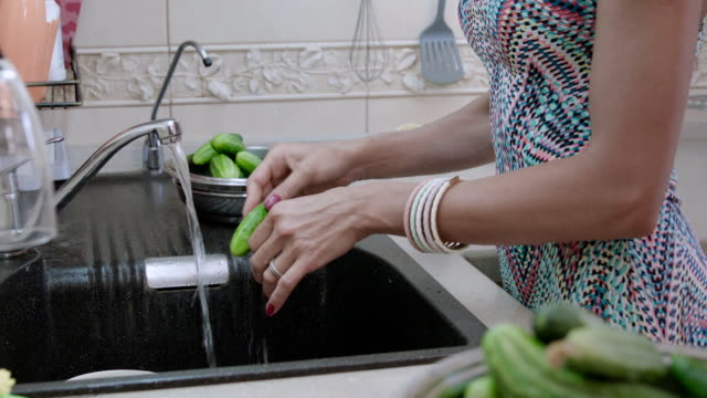 woman washes cucumbers in kitchen sink - turning on or off stock videos and b-roll footage
