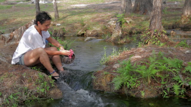 Woman washing a pan in a mountain creek while refreshing her fet.