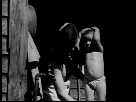 1935 b/w ms woman washing baby standing in diaper with hands on head / usa - 1935 stock videos & royalty-free footage