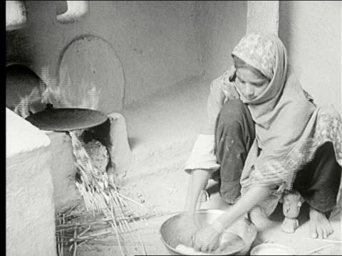 woman washing childs face with water from jug woman build fire under pot with straw making unleavened bread in a dish kneads bread and drops onto pan... - spice stock videos and b-roll footage