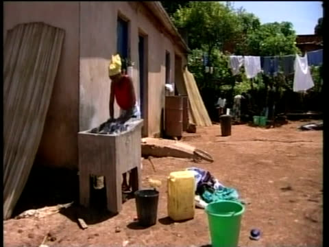 stockvideo's en b-roll-footage met woman washing clothes at outside sink uiga - kleding