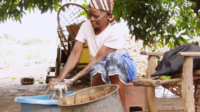 ms woman washing clothes / lukuzi, eastern, zambia - washtub stock videos and b-roll footage