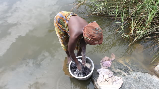 Woman washing clothing by hand in bucket in Lake Tanganyika Burundi gained it's full independence in 1962 having been a Belgian colony from 1916 In...