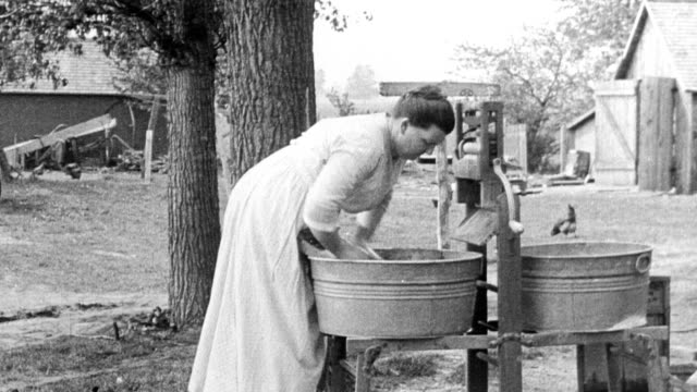 woman washing clothing by hand in wash tub / woman milking cow / woman using hand water pump to pump water into pail / woman churning butter by... - milking stock videos & royalty-free footage