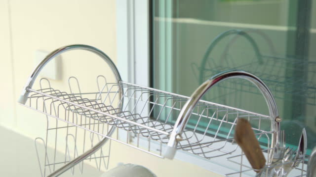 woman washing dishes and bowls in kitchen sink. - dishcloth stock videos & royalty-free footage