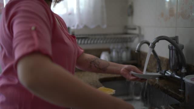 vídeos de stock, filmes e b-roll de mulher lavando pratos em casa - lavando louça