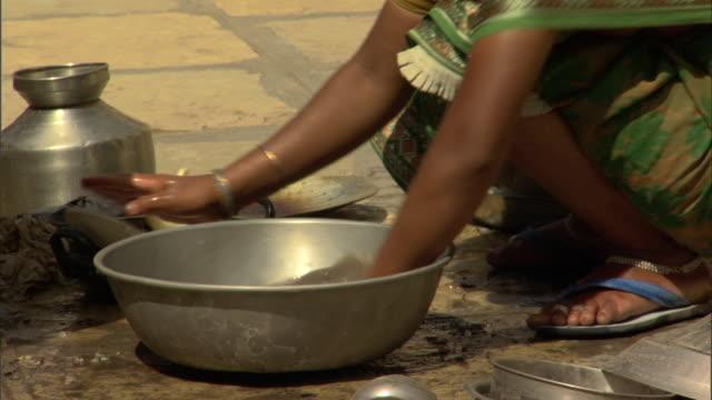 MS TU Woman washing dishes in basin, Pune, Maharashtra, India