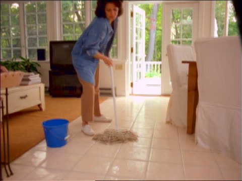 Woman washing floor of house with mop + bucket