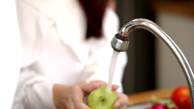 woman washing fresh fruits in her sink at kitchen - environmental conservation stock videos & royalty-free footage