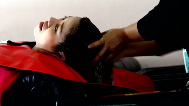 Woman washing hair in beauty salon