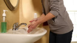 Woman Washing Hands in Bathroom Sink