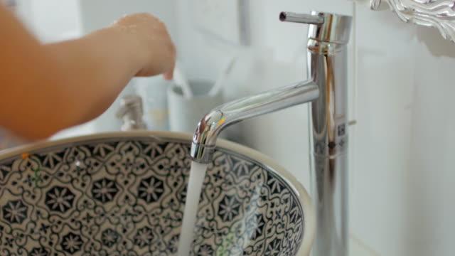 vídeos de stock, filmes e b-roll de mulher lavando as mãos no banheiro - pia instalação doméstica