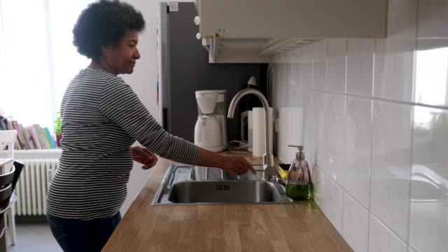 vidéos et rushes de femme se lavant des mains pour empêcher l'infection de virus de la couronne - lavabo et évier