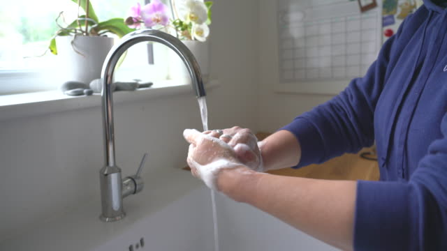 woman washing hands with soap in a kitchen sink - 30 seconds or greater stock-videos und b-roll-filmmaterial