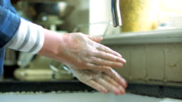 Woman washing hands with soap under running water in kitchen