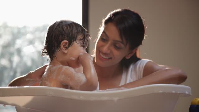 Woman washing her baby in a bathtub