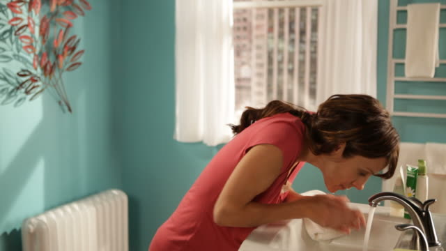MS Woman washing her face in bathroom and clean her face to towel with smiling / Los Angeles, California, United States