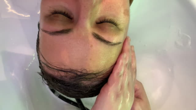 woman washing her hair in hairdresser salon. - hair treatment stock videos and b-roll footage