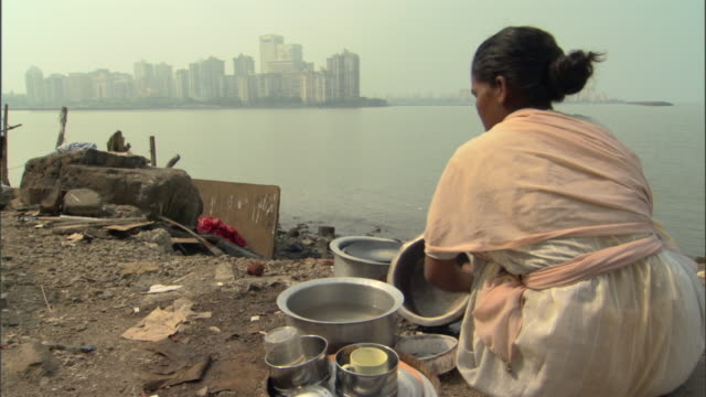 ms woman washing pots and pans on polluted river bank in slums, mumbai, maharashtra, india - poverty stock videos & royalty-free footage