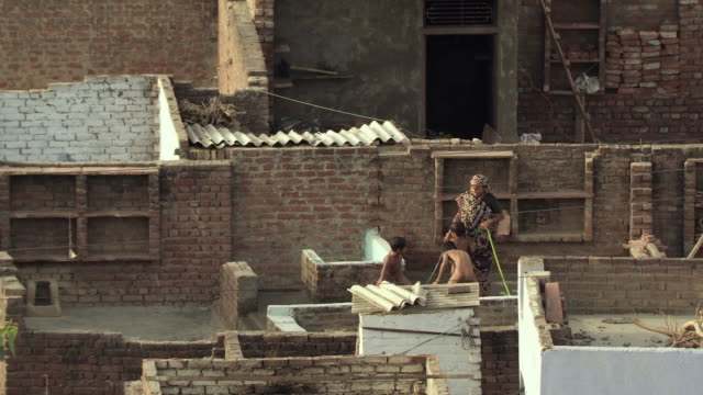 ws ha woman washing three boys with hose on rooftop / agra, uttar pradesh, india - jungen stock-videos und b-roll-filmmaterial