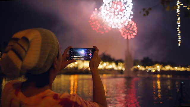 woman watch fire work and shot video - filming stock videos & royalty-free footage