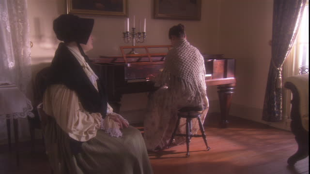 A woman watches a pianist in a 19th century setting.