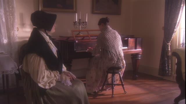 vídeos de stock e filmes b-roll de a woman watches a pianist in a 19th century setting. - reconstituição histórica