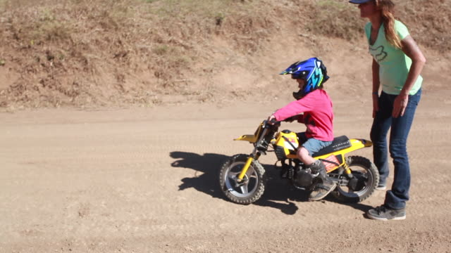a woman watches a young boy ride his dirt bike down a hill on a dirt bike track - kelly mason videos stock videos & royalty-free footage