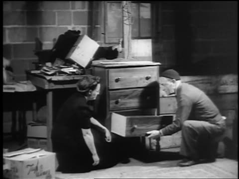 b/w 1943/44 woman watches as man takes broken drawer from bureau in basement / newsreel - kommode stock-videos und b-roll-filmmaterial