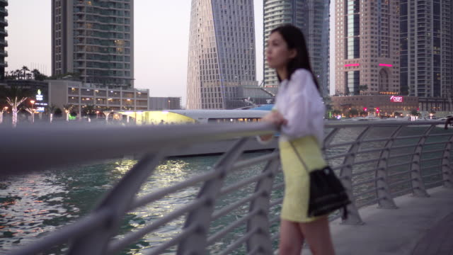 Woman watches bay in Dubai, trucking shot