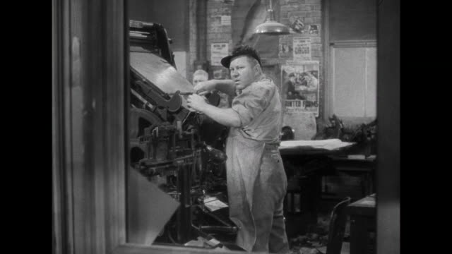 1941 a woman watches disapprovingly while a man attempts to fix a printing press - printer occupation stock videos and b-roll footage