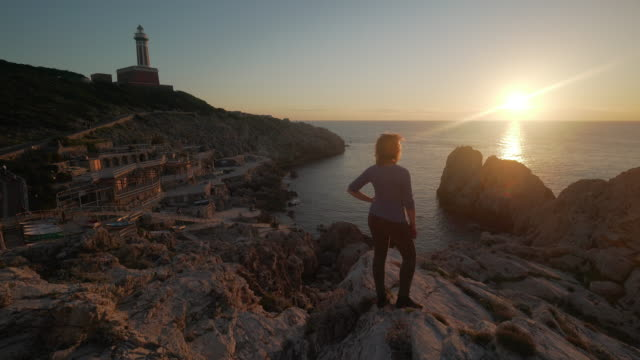 Woman watches lighthouse at sunset on the coast of Capri in Italy