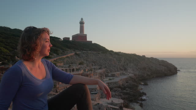 woman watches lighthouse at sunset on the coast of capri in italy - mid length hair stock videos & royalty-free footage