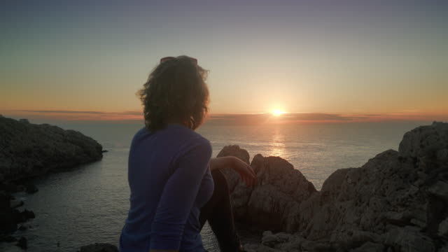 stockvideo's en b-roll-footage met woman watches lighthouse at sunset on the coast of capri in italy - middellang haar