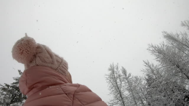 woman watches snowflakes fall in snowy forest - warm clothing stock videos & royalty-free footage