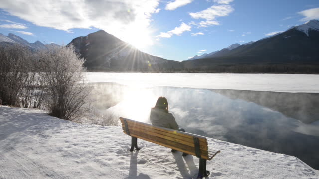 Woman watches steam rise from mountain lake in winter