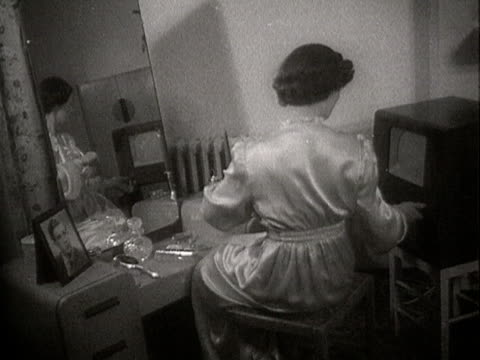 a woman watches television whilst sitting at a dressing table - bathrobe stock videos & royalty-free footage