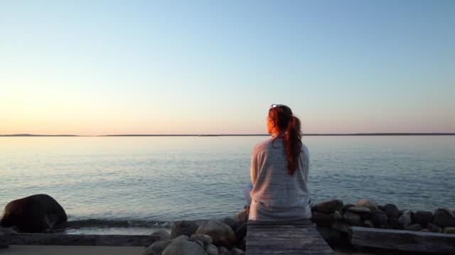 Kvinna klockor på solnedgången från träbrygga genom klippiga lakeshore