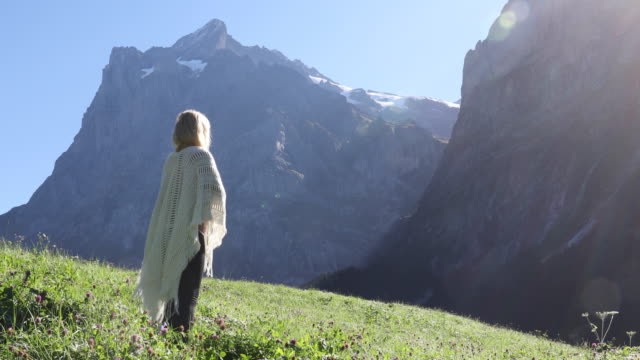 woman watches the sunrise above mountain ridge - shawl stock videos & royalty-free footage