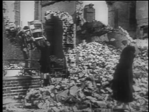 B/W 1940 woman watches two boys grab chair from bombed out building after London Blitz / educational