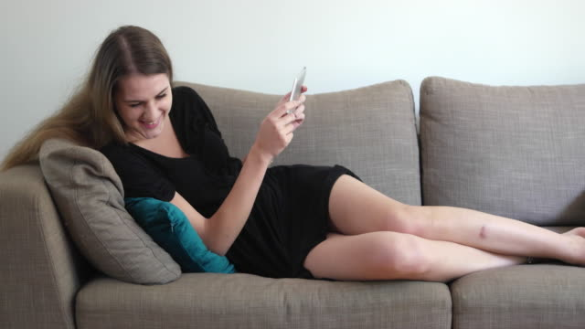 woman watching a funny video online - in den zwanzigern stock-videos und b-roll-filmmaterial