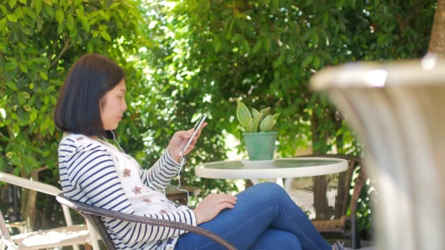 Woman watching a media from smartphone in the garden public park in relax time